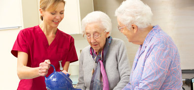 two old women making a coffee assisted by their caregiver
