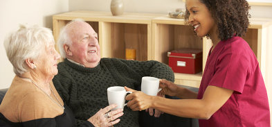 old couple having a cup of coffee assisted by their caregiver