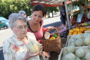 caregiver assisting an old woman buying fruits