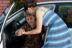 caregiver assisting old woman in getting out of the car